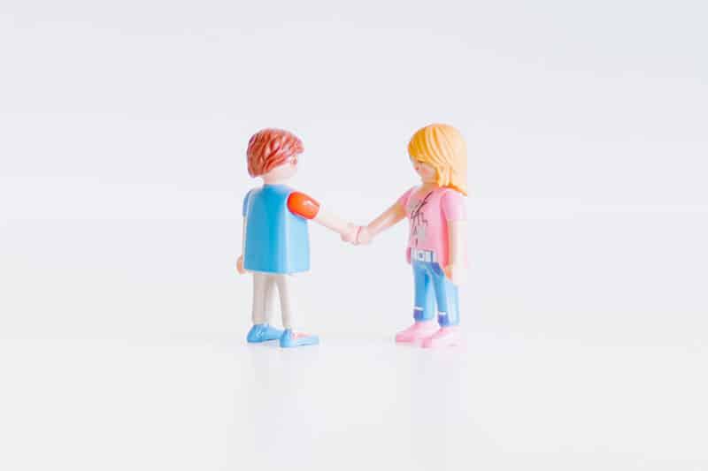 Außergerichtliche Schuldenbereinigung: Erfolgreiche Verhandlung mit Gläubigern. Im Bild: Handshake, symbolisch mit Playmobil-Figuren.